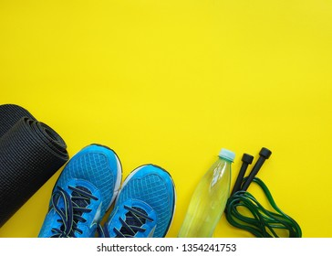 Fitness background. Equipment for gym and home. Jump rope,  mat, water, sneakers  on yellow background top view copy space