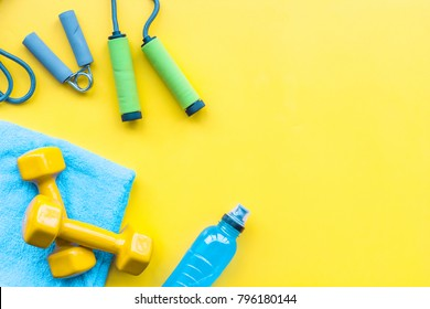 Fitness background. Equipment for gym and home. Jump rope, dumbbells, expander, mat, water on pastel yellow background top view copy space