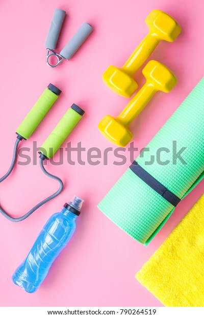Fitness background. Equipment for gym and home. Jump rope, dumbbells, expander, mat, water on pastel pink background top view