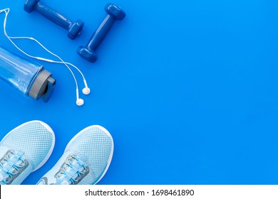 Fitness background with sneakers, dumbbells and headphones on blue table top view copy space