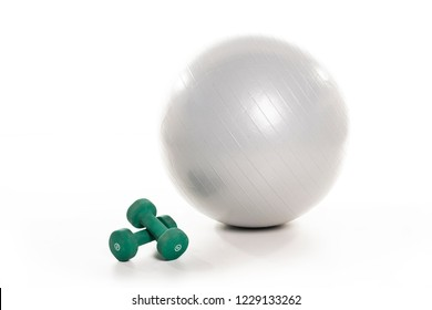 A Fitness ball and dumbell on the white floor studio