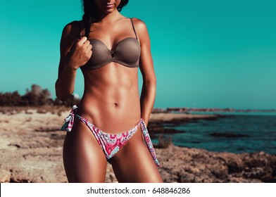 Fitness beach woman posing in the sun showing her fit body