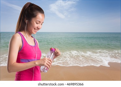 Fitness beautiful woman drinking water and sweating after exercising on summer hot day in beach.
