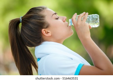 Fitness beautiful woman drinking water after jogging and sweating after sport exercising at summer park. Female athlete after training work out. Sporty Young girl Drink Water After Training outdoors.