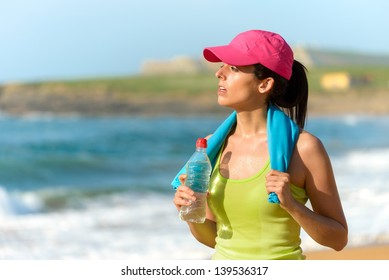 Fitness beautiful woman holding water bottle and sweating after exercising on summer hot day in beach. Female athlete after work out.