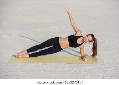 Fitness beautiful woman strength training her body core muscles with yoga pose. Athlete planking on one arm doing side plank and hip lift.