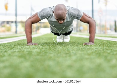 Fitness black man exercising push ups listening to music with headphones. Male model cross-training in urban background. African guy in his twenties doing workout outdoors in the street.