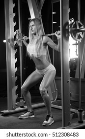Fitness blond fit woman in gym with barbell