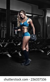 fitness blonde girl posing and prepares for exercising with dumbbell in gym