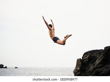 "Fitness body young age man jumping into the void (bottom is not seen) from a rock, concept of freedom and ""carpe diem""."