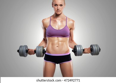 fitness bodybuilder woman with dumbbells.beautiful blonde girl with muscles.gym