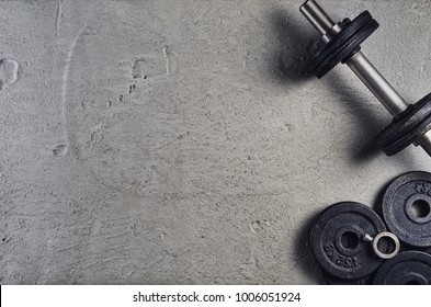 Fitness or bodybuilding concept background. Product photograph of old iron dumbbells on grey, conrete floor in the gym. Photograph taken from above, top view with lots of copy space
