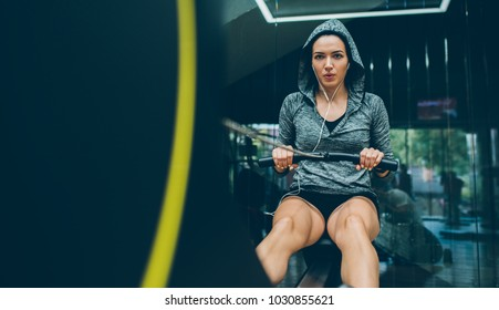 Fitness, bodybuilding, people, healthy lifestyle and sport concept. Beautiful fit brunette woman is doing exercises for legs in the gym, sporty woman exercising with barbell in the gym.
