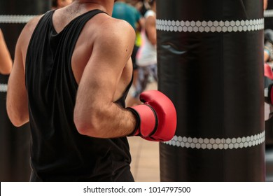 Fitness and Boxing Workout: Boy with Red Gloves and Black Punching Bag.