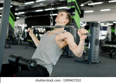 Fitness Caucasian man working out shoulder pull down at gym. Man strength training using lat pulldown machine.