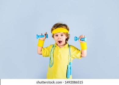 Fitness child. Sporty boy with jump rope and dumbbells. Gym workout. Boy in sportwear with skipping rope and dumbbells. Child sportsman. Childhood activity. Sport. Fitness, health and energy. Success.