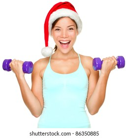 Fitness christmas woman training lifting hand weight wearing santa hat. Female model working out smiling happy and excited isolated on white background.