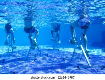 Fitness class doing aqua aerobics on exercise bikes in swimming pool resort hotel