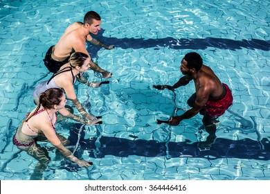 Fitness class doing aqua aerobics on exercise bikes in swimming pool