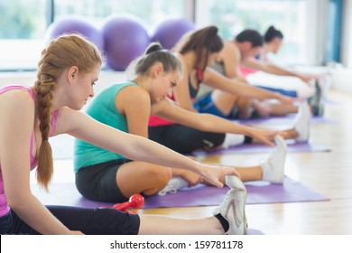 Fitness class and instructor stretching legs in bright exercise room