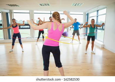 Fitness class and instructor swinging hula hoops at the waist in bright room