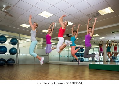 Fitness class jumping up in studio at the gym