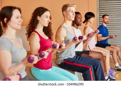 Fitness class making together exercise with dumbbells