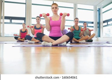 Fitness class and serious trainer lifting dumbbells in the gym