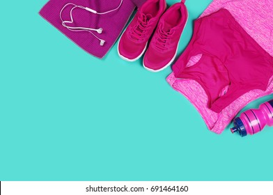 Fitness clothes and equipment laying on a teal color background view from above