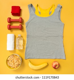 Fitness clothing, dumbbells and natural food. Fitness and healthy lifestyle flatlay on yellow background.