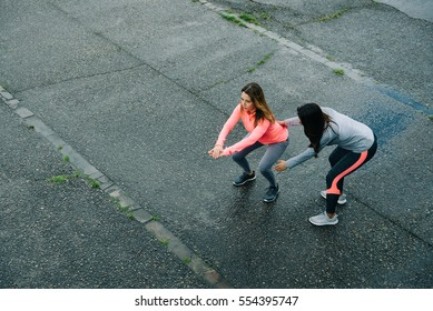 Fitness coach correcting squat posture. Two female athletes working out outside during winter rainy day.