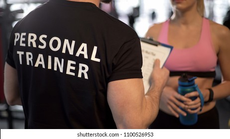 Fitness coach explaining training program and schedule to female client in gym