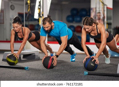 Fitness coach and girls doing crossfit workout with medicine balls