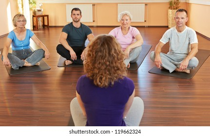 Fitness coach giving group yoga instructions in a gym
