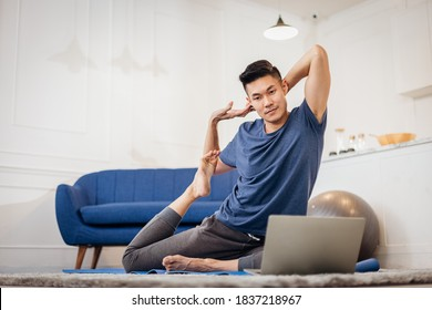 Fitness coach teaching yoga online to group of people. Young asian man beginning yoga practice with private teacher via video conference.