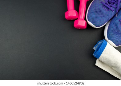 Fitness concept background with sneakers, dumbbells and towel. Top view with space for your text.