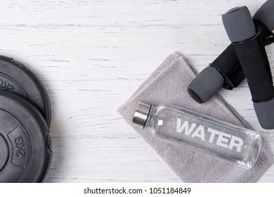 Fitness concept, bottle of water, dumbbells and weight plates on