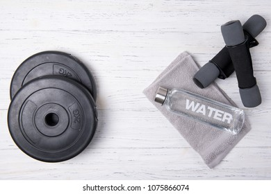 Fitness concept, bottle of water, dumbbells and weight plates on wooden background, top view