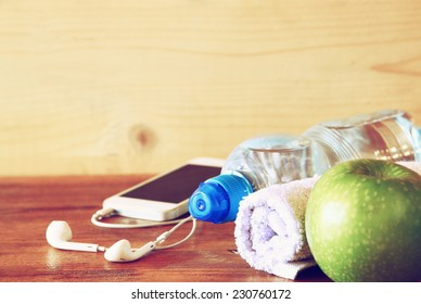 fitness concept with bottle of water, mobile phone and earphones, towel ,apple over wooden background.
