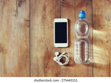 fitness concept with bottle of water, mobile phone with earphones over wooden background. filtered image