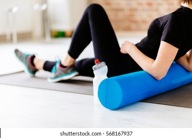 Fitness concept. Close up of woman relaxing after workout on the exercising mat.Portrait of Active Tired Woman Using Foam Roller in Light Room.