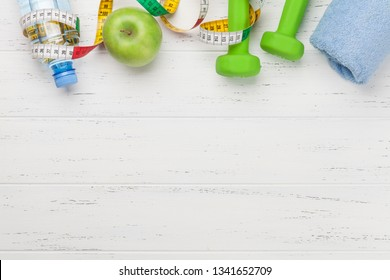 Fitness concept. Dumbbells, tape measure and water bottle on wooden background. Top view with space for your text