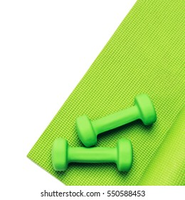 Fitness concept - green yoga mat and dumbbells on the white background