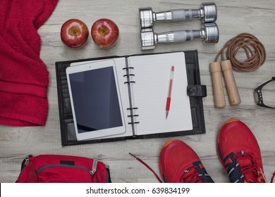 Fitness concept and healthy lifestyle with diary and tablet PC, pencil, apples, dumbbells, skipping rope, towel, trainers, backpack and heart rate watch