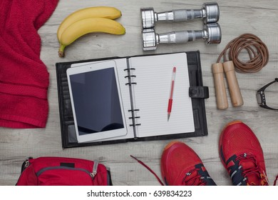 Fitness concept and healthy lifestyle with diary and tablet PC, pencil, bananas, dumbbells, skipping rope, towel, trainers, backpack and heart rate watch