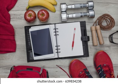 Fitness concept and healthy lifestyle with diary and tablet PC, pencil, apples, bananas, dumbbells, skipping rope, towel, trainers, backpack and heart rate watch