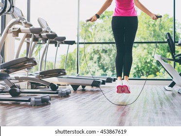 Fitness concept. Healthy lifestyle. Young slim woman jumping with skipping rope in gym.