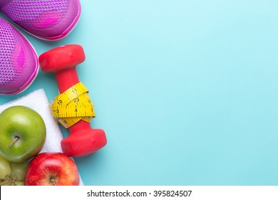 Fitness concept with mix fruits, dumbbells, measuring tape and sport shoes on bright cyan background.