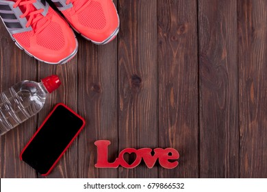 Fitness Concept with Mobile Phone. Top view image. Women's Accessories for Sports. Kit Sports stuff over Brown Background