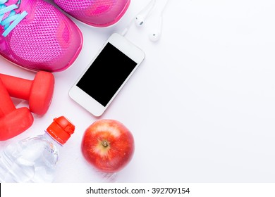 fitness concept with mobile phone, towel, shoes, dumbbells, red apple and woman sport footwear over white background. View from above
